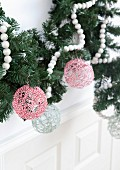 Christmas baubles hand-made from cord and hung from garland