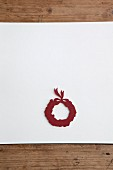 Christmas wreath cut out of red paper on white surface