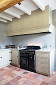 Simple country-house kitchen in natural shades with terracotta floor tiles