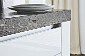 A granite worktop over white kitchen drawers