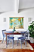 Blaue Windsorstühle um einen Holztisch vor einer alten Weltkarte