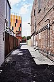 Ramshackle alley between two brick houses