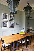 Antique lamps above dining table in front of artworks on panelled wall