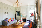 Colourful upholstery in living room with panelled walls and fireplace