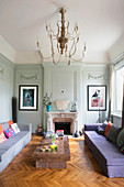 Colourful cushions on two sofas facing one another in front of open fireplace