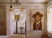 Portrait of Native American wearing hat in bedroom with view into bathroom