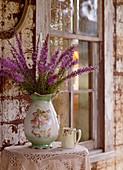 Vintage-style vase of flowers against battered wall