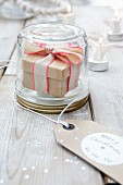 Gift box with ribbon in screw-top jar with 'Merry Christmas' tag