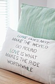 Hand-made cushion cover with printed and embroidered motto