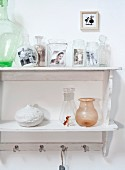 Vintage photos in glass vessels on wall-mounted shelf