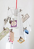 Various cards clipped to wire lampshade
