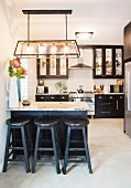 Kitchen with black cupboards and bar stools next to counter with marble top
