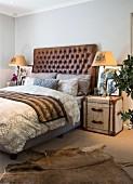 Schlafzimmer mit Betthaupt aus Leder, Überseekoffer als Nachtkästchen und Tierfellteppich