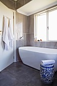 White bathtub and blue and white ceramic drum stool in modernised bathroom