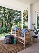 Zwei Korbsessel mit blau gemusterten Kissen auf überdachter Terrasse
