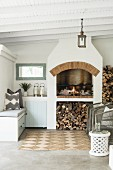 Firewood stacked below fireplace and lounge furniture on roofed veranda