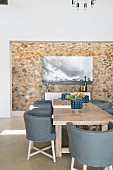 Designer chair and stone-clad wall in elegant dining area