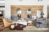 Grey upholstered furniture and stone-clad wall in elegant lounge
