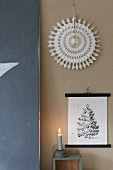 Festive arrangement of picture, paper sunburst and lit candle against wall