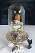 Easter arrangement under glass cover, egg shells, feathers and napkin bunny