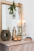 Madonna figurine, arrangement of candles and large mirror on cabinet
