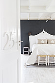 Number on open interior door with view into white bedroom with black wall