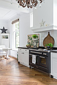 Modern gas cooker in white country-house kitchen with dining area
