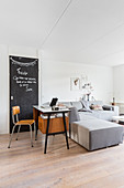 Retro desk and chalkboard behind modern grey sofa