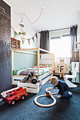 Boy playing on floor next to bed in bedroom