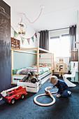 Junge spielt vor dem Bett auf dem Boden im Kinderzimmer