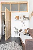 Sofa in small room behind open door below row of interior windows