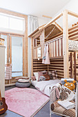 Pink rug and striped wooden bunk beds in children's bedroom