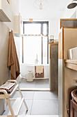 Verwinkeltes Badezimmer in Naturtönen mit großem Fenster