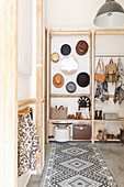 Patterned rug in font of simple coat rack made from cellar shelving