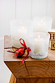 Three white lanterns with lace braids on a wooden stool