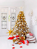 Wrapped gifts around golden Christmas tree in front of the glass door