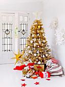 Verpackte Geschenke um goldenen Weihnachtsbaum vor der Glastür