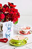 In alte Sammeltassen gegossene Kerzen auf dem Tisch mit Blumen