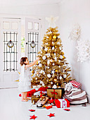 Girl with angel wings in front of golden Christmas tree