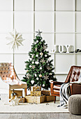 Leather armchairs and gifts around the Christmas tree in front of a cassette wall
