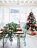 Festive table with flower garland and decorated Christmas tree