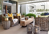 Wicker furniture and rustic coffee table made from untreated wooden beams on patio
