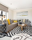 Various scatter cushions on grey corner couch, coffee table and black and white rug