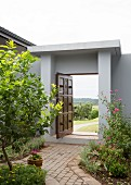 Open wooden door in modern grey garden wall