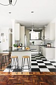 Kitchen counter and black and white tiled floor in white fitted kitchen