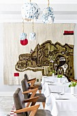 Set tables in restaurant with abstract wall hanging in background