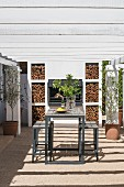 Wooden table, bar stools, barbecue and pergola on terrace
