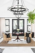 Chandelier and wicker armchairs in elegant foyer