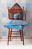 Blue and white, patterned still-life arrangement on chair against wallpaper