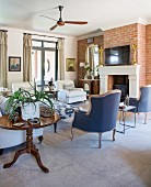 Various armchairs and fireplace in brick wall in living room